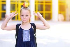 Liten flickaanseende med Apple på hennes huvud arkivbild