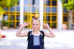 Liten flickaanseende med Apple på hennes huvud royaltyfri bild