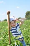 Liten flickaanseende med skyffeln bland potatisbuskar Royaltyfri Foto