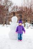 Liten flickaanseende nära snögubben Royaltyfri Bild