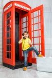 Liten flickaanseende på ett telefonbås Royaltyfri Bild