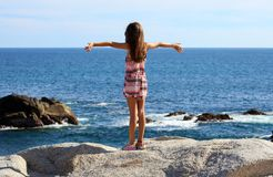 Liten flickaanseende på klippan på havframdelen i havet för Los Cabos Mexico semesterortklippa Royaltyfri Bild