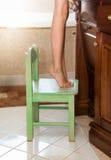 Liten flickaanseende på tåspetsarna på stol på badrummet arkivbilder