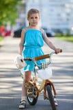 Liten flickaanseendet med cykeln parkerar in Royaltyfri Foto