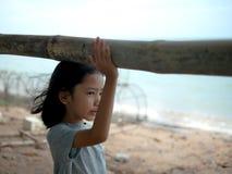 Liten flickaanseendet vid styreräcket vid havet Asiatisk flicka som framåtriktat ser på stranden arkivfoto