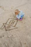 Liten flickaattraktioner i sanden arkivbilder