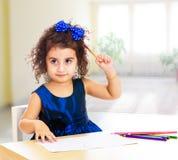Liten flickaattraktioner på tabellen med blyertspennor royaltyfria foton
