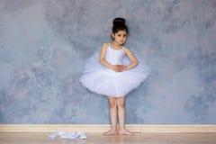 Liten flickaballerina i en vit ballerinakjol arkivbild