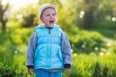 Liten flickabarn i ett fält med grönt gräs och den blommande tulpan royaltyfri fotografi