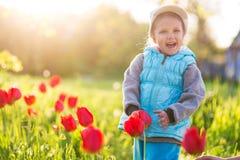 Liten flickabarn i ett fält med grönt gräs och den blommande tulpan arkivfoton