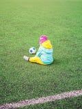 Liten flickabarn på fotbollfält, i sportswearen som utbildar royaltyfria foton
