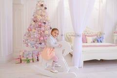 Liten flickabarn som spelar i rum för barn` s på rosa bakgrund Royaltyfri Bild