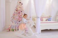 Liten flickabarn som spelar i rum för barn` s på rosa bakgrund Royaltyfria Bilder