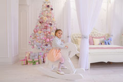 Liten flickabarn som spelar i rum för barn` s på rosa bakgrund Royaltyfri Fotografi
