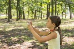 Liten flickabarnet av 8 år som ser kamerasammanträde på grön gräsmatta i stad, parkerar flicka 8 år i parkera som tar bilder av n fotografering för bildbyråer