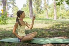 Liten flickabarnet av 8 år som ser kamerasammanträde på grön gräsmatta i stad, parkerar flicka 8 år i parkera som tar bilder av n royaltyfri foto