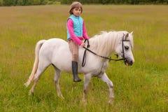 Liten flickabarnet går på en vit häst på fältet utomhus Arkivfoto