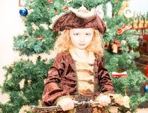 Liten flickabarnet klädde som piratkopierar för allhelgonaafton på bakgrund av julgranen Royaltyfri Bild