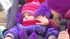 Liten flickablick på hennes nyfödda syster i barnvagn 4K UltraHD, UHD arkivfilmer
