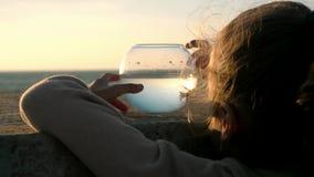 Liten flickablickar och lekar fiskar det runda akvariet utomhus på solnedgången på kusten stock video