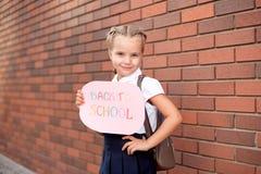 Liten flickablondin i ställningar för skolalikformig nära en tegelstenvägg som rymmer en svart tavla med textbaksidan till sk royaltyfri bild