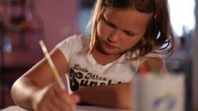 Liten flickablondinen drar en blyertspenna сlose-up suddighet bakgrund arkivfilmer