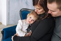 Liten flickacloseupen i omfamningar av föräldrar Stående av en lycklig familj av person tre Arkivbilder