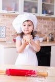 Liten flickadanandedeg på kök royaltyfri bild