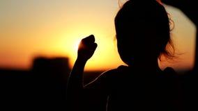 Liten flickadans i solnedgången på balkongen Konturnärbildskott stock video
