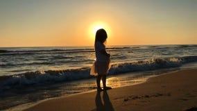Liten flickadans p? stranden p? solnedg?ngen lager videofilmer