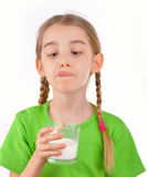 Liten flickadrinkar mjölkar från ett exponeringsglas Royaltyfria Bilder