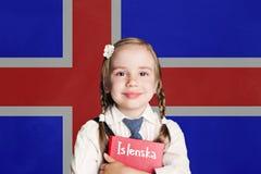 Liten flickaelev med boken mot den Island flaggabakgrunden Lär det isländska språket, det Island begreppet fotografering för bildbyråer