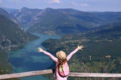 Liten flickafotvandrare med händer upp på berget royaltyfri foto