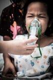 Liten flickagråt, medan få i inhalatormaskering i sjukhus Royaltyfri Foto