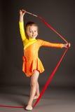 Liten flickagymnastik med bandet arkivfoto