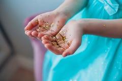 Liten flickahänder som täckas med guld som blänker stjärnor Arkivfoton