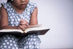 Liten flickahänder vek i bön på en helig bibel Royaltyfri Bild