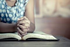 Liten flickahänder vek i bön på en helig bibel Royaltyfria Bilder