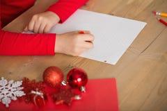 Liten flickahandstilbokstav till santa på jul fotografering för bildbyråer