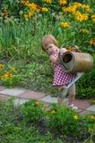 Liten flickahjälp bevattnar blommorna Royaltyfri Bild