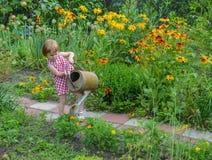 Liten flickahjälp bevattnar blommorna Royaltyfria Bilder
