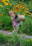 Liten flickahjälp bevattnar blommorna Arkivfoton