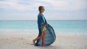 Liten flickahvegyckel på stranden Ungen tycker om strandsemester med pareo stock video
