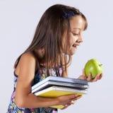 Liten flickainnehav bokar och ett äpple royaltyfri bild