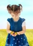 Liten flickainnehav i händerna av en stor fjäril fotografering för bildbyråer