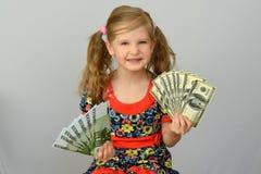 Liten flickainnehavet räcker in en packe av dollar och euro Arkivbild