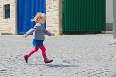Liten flickakörningar längs gatan, kullersten Arkivfoton
