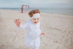 Liten flickakörningar längs stranden royaltyfria bilder