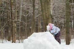 Liten flickaklättringöverkant av den snöig kullen in Royaltyfri Fotografi
