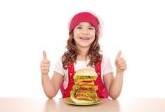 Liten flickakock med den stora hamburgaren och tummar upp Royaltyfri Foto